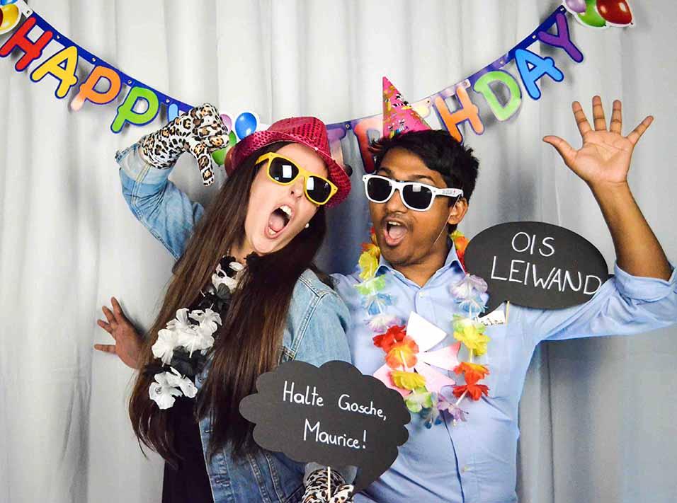 junge Frau und junger Mann mit Hüten, Sonnenbrillen und Hawaiketten