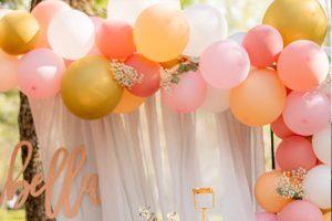 Luftballongirlande vor weißem Vorhang
